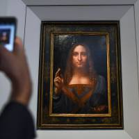 A journalist takes photos of Leonardo da Vinci's 'Salvator Mundi' after it was unveiled at Christie's in New York on Tuesday. One of fewer than 20 paintings by Leonardo da Vinci and the only one in private hands, the work will be offered in Christie's Evening Sale of Post-War and Contemporary Art on Nov. 15. | AFP-JIJI