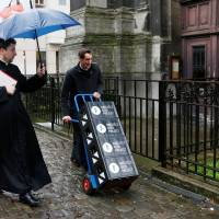 Belgian priests Kurt and Jeremie deliver crates of a new beer called Ste Kat' to restaurants and cafes surrounding the Sainte-Catherine church, as they are launching the new beer to raise funds for renovation works on the building in Brussels Thursday. | REUTERS