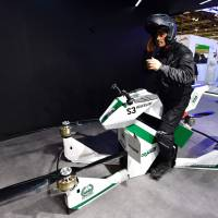 An Emiratee police officer stands next to a drone motorcycle at the Gitex 2017 exhibition at the Dubai World Trade Center in Dubai, UAE, Sunday. | AFP-JIJI