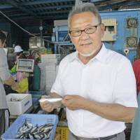 Osamu Oka, head of a fishery cooperative in the city of Kishiwada, Osaka Prefecture, holds a sardine caught off the city's Jizohama district in August. | KYODO