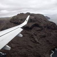 A picture taken from the inaugural first commercial flight between Johannesburg and Saint Helena shows the cliffs of the volcanic tropical island of Saint Helena, in the South Atlantic Ocean and part of the British Overseas Territory, on Saturday. | AFP-JIJI
