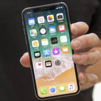 An attendee displays an Apple Inc. iPhone X for a photograph during an event in Cupertino, California in September. | BLOOMBERG