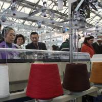 Chinese visitors look at a knitting machine at 'Shanghaitex 2003,' the 10th International Exhibition on Textile Industry, in Shanghai, China in 2003. | BLOOMBERG NEWS
