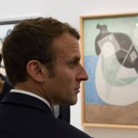 French President Emmanuel Macron stands by Pablo Picasso's 1932 painting 'Woman lying in the sun' during the opening of the 'Picasso 1932: Erotic Year' exhibition at the Picasso museum in Paris, on Sunday. | IAN LANGSDON / POOL / VIA AFP-JIJI