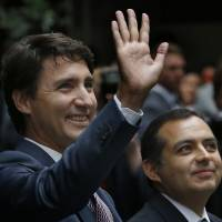 Accompanied by Mexican Senate President Ernesto Cordero (right), Canadian Prime Minister Justin Trudeau waves upon his arrival to the Mexican Senate in Mexico City Friday. Trudeau said in a speech to the senate Friday that support for NAFTA 'depends on the fruits of this trade being fairly shared.' | AP