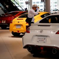 A man looks around a Nissan showroom at the carmaker's headquarters in Yokohama. | REUTERS