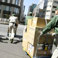 Yamato Transport workers push trolleys stacked with parcels through Tokyo's Ginza district in March. On Sunday, the firm hiked delivery prices to offset rising labor costs. | KYODO