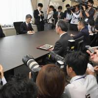 Kobe Steel Ltd. Chairman and President Hiroya Kawasaki (left) meets with an industry ministry official Thursday in Tokyo over the firm's data falsification scandal. | KYODO