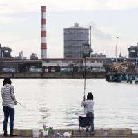People fish along a promenade as a Kobe Steel Ltd. plant stands in the background in Kakogawa, Hyogo Prefecture on Oct. 14. | BLOOMBERG