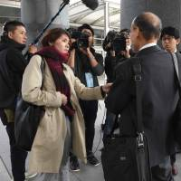 Journalists interview a shareholder before an extraordinary Toshiba shareholders meeting in the city of Chiba on Tuesday. | AFP-JIJI