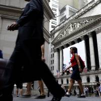 People pass the New York Stock Exchange in 2015. Congress is looking for ways to raise revenue, and one of the methods reportedly under consideration is to limit how much pretax money workers can contribute to their 401(k) and similar accounts. If it were to happen, the move would strike at a way that tens of millions of Americans use to save for retirement. | AP