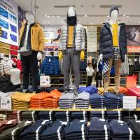 Jackets are displayed on mannequins at a Uniqlo store in the Orchard Central shopping mall in Singapore on Tuesday. | BLOOMBERG