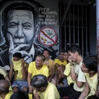 Inmates are seen beside a wall depicting Philippine President Rodrigo Duterte as authorities search for contraband at the Manila City Jail on Monday. | AFP-JIJI