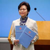 Hong Kong Chief Executive Carrie Lam poses with copies of her policy speech in the city on Wednesday. | REUTERS