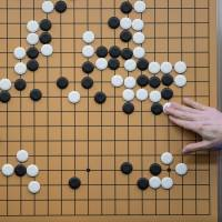 A commentator in a media room positions pieces forming a replica of a game between go player Lee Se-Dol and Google-developed AlphaGo in Seoul on March 13, 2016. | AFP-JIJI