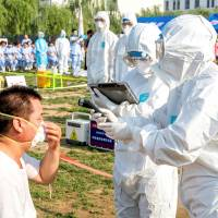 People participate in an emergency exercise on prevention and control of the H7N9 bird flu virus organized by the Health and Family Planning Commission of the local government in Hebi, Henan province, China, in June. | REUTERS