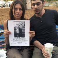 Chrystal Couto holds a poster of her grandmother as Aaron Austin looks on in Santa Rosa, California, on Friday. The couple, from Redway, are searching for Couto's grandmother and her husband, who haven't been heard from since a wildfire tore through their Santa Rosa neighborhood. They are hanging flyers in evacuation centers with photos of the older couple. | AP