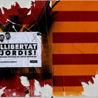 A damaged sticker of a Spanish and Catalan flag and a placard reading 'Freedom to Jordis!' in reference to leaders of two of the largest Catalan separatist organizations, Catalan National Assembly's Jordi Sanchez and Omnium's Jordi Cuixart, who were jailed by Spain's High Court, are seen in Barcelona, Spain, Sunday. | REUTERS