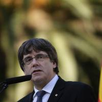 Catalan regional President Carles Puigdemont addresses the media after a ceremony commemorating the 77th anniversary of the death of Catalan leader Lluis Companys at the Montjuic Cemetery in Barcelona, Spain, Sunday. Catalonia's president is facing a critical decision that could determine the course of the region's secessionist movement to break away from Spain. The Spanish government has given Carles Puigdemont until Monday morning to clarify if he did or didn't actually declare independence last week. | AP