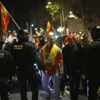Catalan police officers stand to prevent Spanish demonstrators from moving forward during a march against the unilateral declaration of independence approved earlier by the Catalan parliament in downtown Barcelona on Friday. | AP