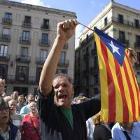 A man waves a stelada (pro-independence Catalan flag) during a protest against the arrest of two Catalan separatist leaders in Barcelona on Tuesday. | AFP-JIJI