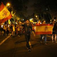 Anti-independence demonstrators waving Spanish flags march blocking main Diagonal avenue during a protest in Barcelona, Spain, Wednesday. Catalonia's regional government is mulling when to declare the region's independence from Spain in the wake of a disputed referendum that has triggered Spain's most serious national crisis in decades. | AP