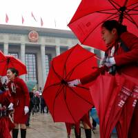 Ushers manage delegates' umbrellas at the opening session of the Chinese Communist Party congress on Wednesday at the Great Hall of the People in Beijing. | REUTERS