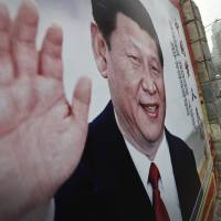 Women walk by a poster featuring Chinese President Xi Jinping in Beijing on Thursday. | AP