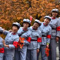 Women in replica Chinese Red Army uniforms have their photo taken in front of autumnal leaves in Beijing on Friday. | REUTERS