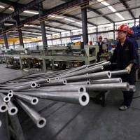 Workers are seen in a Qinghai Guoxin Aluminum Industry Inc. Co. workshop in Xining, Qinghai province, on Friday. | REUTERS