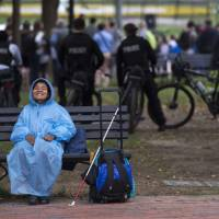 A woman sits on a bench smiling as it starts to rain near the White House in Washington Thursday. | AFP-JIJI