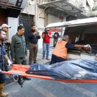 Syrian security forces carry the remains of a reported suicide bomber following an attack near the main police headquarters in Syria's capital Damascus on Wednesday. Three suicide bombers blew themselves up near the main police headquarters, killing at least two people, the interior ministry said. | AFP-JIJI