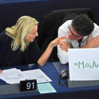 An Austrian member of the European Parliament, Evelyn Regner (left), and French MEP Patrick Durand talk Wednesday during a debate about sexual harassment in Strasbourg, France. The placard refers to the hashtag #MoiAussi (#MeToo). | AFP-JIJI