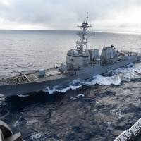 The Arleigh Burke-class guided-missile destroyer USS Chafee pulls alongside the aircraft carrier USS Nimitz for a scheduled replenishment at sea in October last year. | U.S. NAVY