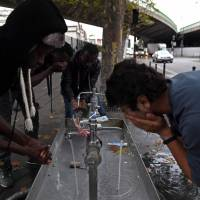 Migrants wash themselves from a sink installed on a street of Paris on Wednesday. Unprecedented waves of migration are affecting the world today, with record numbers of people escaping war-torn regions, poverty, persecution and natural disasters. | AFP-JIJI