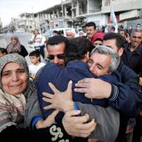 Relatives hug one of the hostages held by Islamic State militants who escaped from his captors in Qaryatayn town in Homs province, Syria, Sunday. | REUTERS