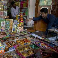 An Indian shopkeeper sells fire crackers in New Delhi on Monday, ahead of the upcoming Diwali festival. India's Supreme Court the same day banned the sale of fireworks in the capital and nearby towns in a move to curb air pollution. | AP
