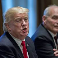 U.S. President Donald Trump speaks as John Kelly, White House chief of staff, listens during a briefing with senior military leaders in the Cabinet Room of the White House in Washington on Thursday.   BLOOMBERG