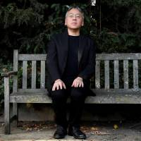 Kazuo Ishiguro poses for the media outside his home in London on Thursday after winning the Nobel Prize in literature. | REUTERS