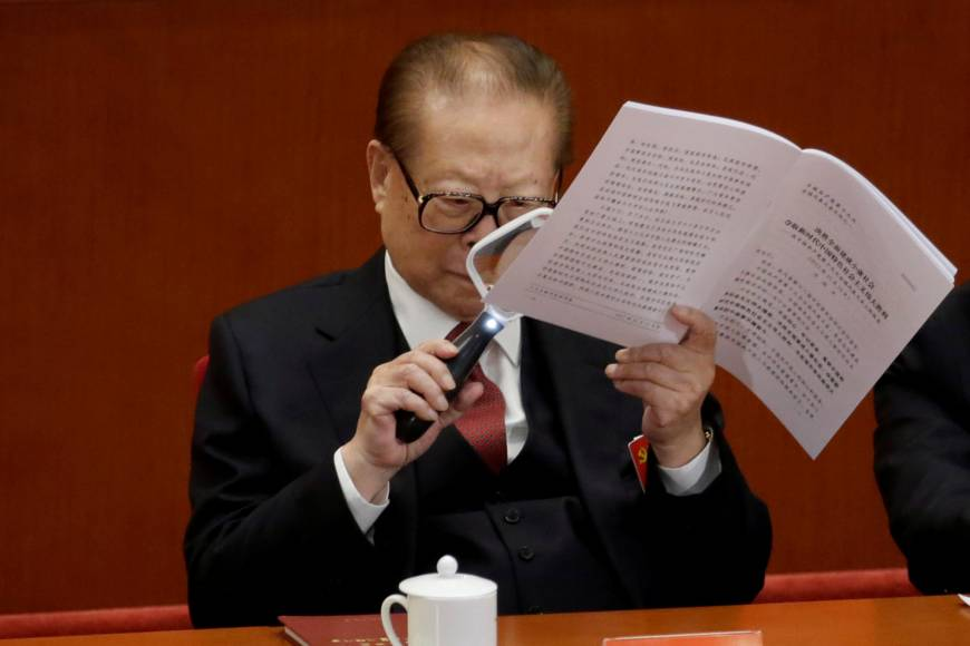Former Chinese President Jiang Zemin uses a magnifying glass as he reads current leader Xi Jinping's report during the opening of the 19th National Congress of the Communist Party of China at the Great Hall of the People in Beijing on Wednesday. | REUTERS