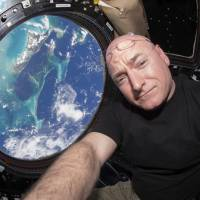 In this 2015 photo, astronaut Scott Kelly takes a photo of himself inside the Cupola, a special module of the International Space Station that provides a 360-degree viewing of the Earth and the station. In his new autobiography, the retired astronaut writes about his U.S. record-breaking year in space and the challenging life events that got him there. | SCOTT KELLY / NASA / VIA AP
