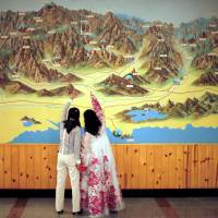 People point to a map on a wall at the Mount Kumgang resort in Kumgang, North Korea, in September 2011. | REUTERS
