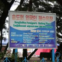 A sign in English, Russian and Korean marks the foreigners-only section of Songdowon Beach in Wonsan, North Korea, in August 2010. | RAYMOND CUNNINGHAM / VIA REUTERS