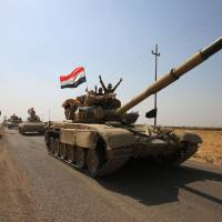 Iraqi forces drive towards Kurdish peshmerga positions on Sunday on the southern outskirts of Kirkuk. The presidents of Iraq and Iraqi Kurdistan held talks to defuse an escalating crisis, after a deadline for Kurdish forces to withdraw from disputed positions was extended by 24 hours. | AFP-JIJI