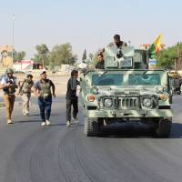 Volunteers and peshmerga forces carry their weapons north of Kirkuk, Iraq, Monday. | REUTERS