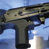 A device called a 'bump stock' is attached to a semi-automatic rifle at the Gun Vault store and shooting range in South Jordan, Utah, on Oct. 4. | AP