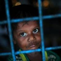A Rohingya refugee boy, who crossed the border from Myanmar this week, takes shelter at Long Beach Primary School, in the Kutupalong refugee camp, near Cox's Bazar, Bangladesh, on Monday. | REUTERS