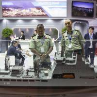Attendees look at a model of a Daewoo Shipbuilding & Marine Engineering Co. ship at the company's booth during an exhibition in Langkawi, Malaysia, in March 2015. | BLOOMBERG