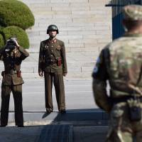 North Korean soldiers look at the South side during a visit to the truce village of Panmunjom in the Demilitarized Zone by U.S. Secretary of Defence Jim Mattis and South Korean Defense Minister Song Young-moo on the border between North and South Korea on Thursday. | AFP-JIJI