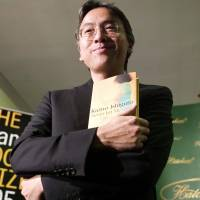 British author Kazuo Ishiguro poses with his book 'Never Let Me Go' in London in October 2005. | AFP-JIJI